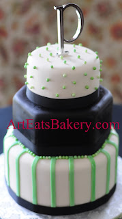 Green, black and white custom modern wedding cake with edible pearls, stripes, and silver monogram topper