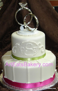 Two tier custom designed sugar pearls, monogram and stripes wedding cake with ring topper and ribbons