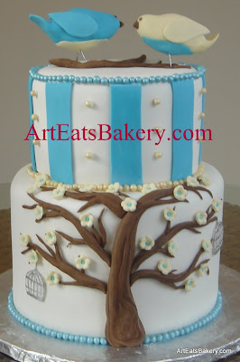 Blue, white and yellow custom creative baby shower cake with stripes, edible pearls, tree, flowers, bird cages and bird topper