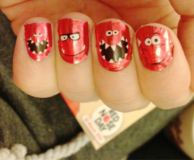 A close up of nails with red nose day nail wraps on