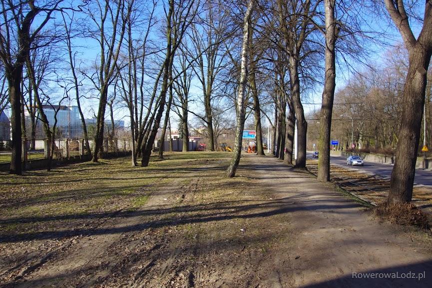 Nieco nad poziomem torowiska i jezdni - pomiędzy drzewami.