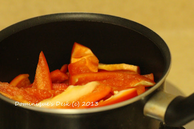Sliced red peppers being saute in a saucepan