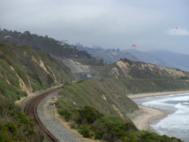 four paragliders in the sky over the freeway, train tracks, and cliff