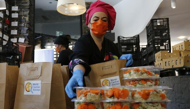 mujer con guantes y cubrebocas coronavirus sirviendo comida espana abril 24 2020 1220784933
