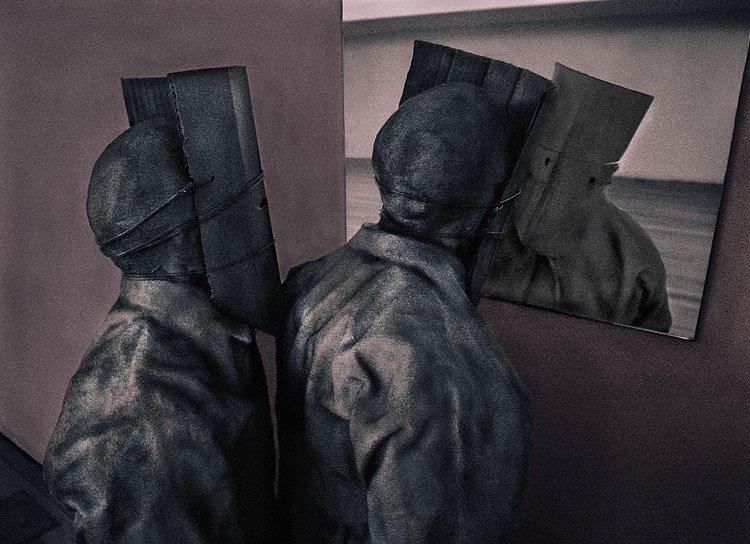 Duas figuras com máscaras na cabeça, olhando-se num espelho