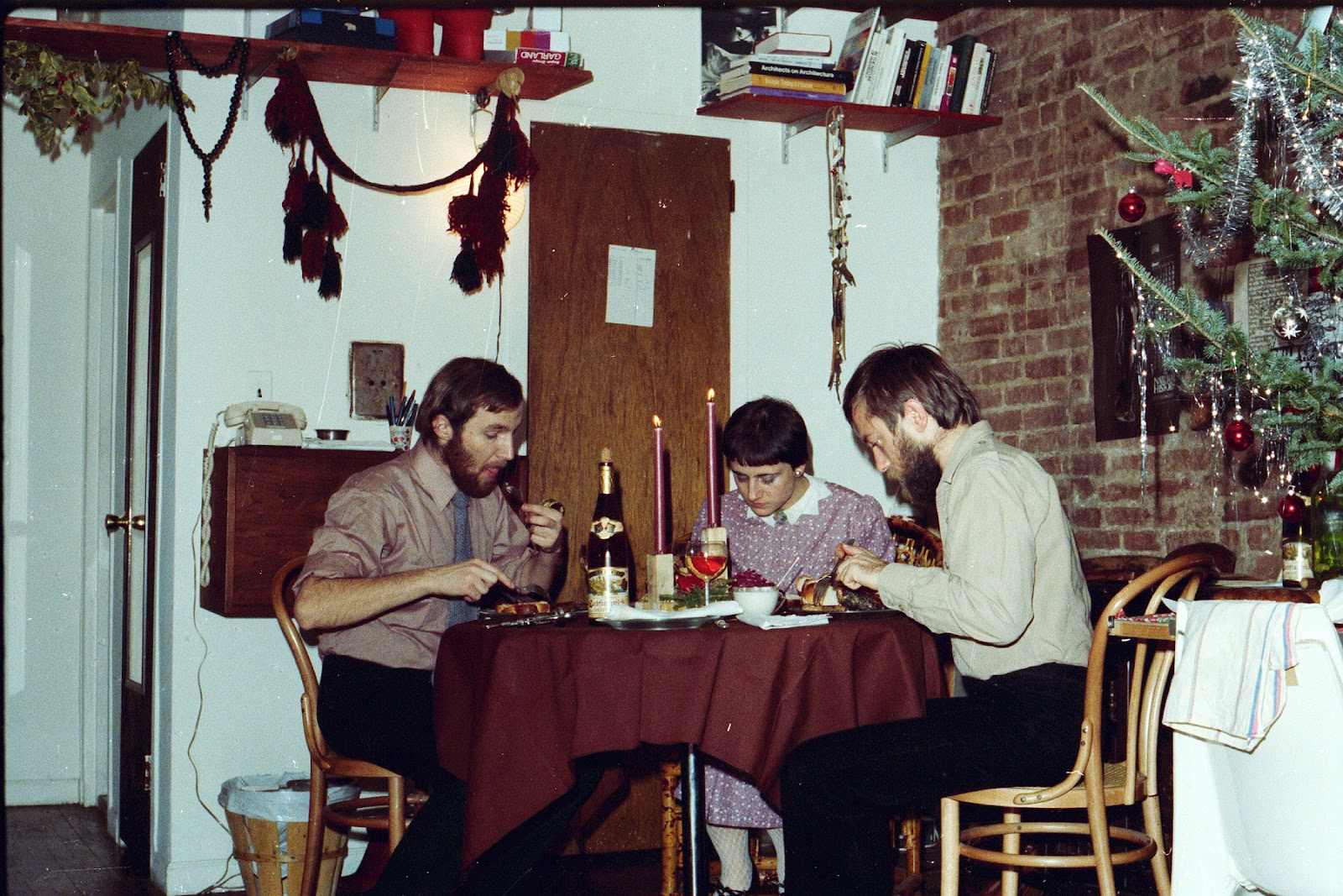 Photo of three adults sitting down at a dinner table.