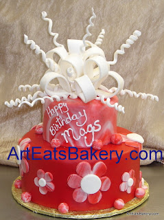 Red and white two tier fondant birthday cake with marbled tier and flowers and sugar bow topper