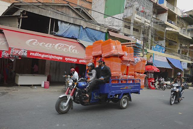 two men carrying large containers on a motorized tricycle cart
