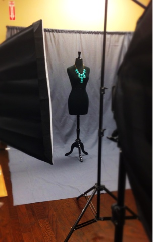 A behind-the-scenes photo showing the photography set, including lighting and backdrop, for a professional photograph of clothing by A Cut Above.