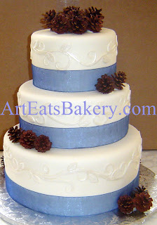 Three tier unique white fondant wedding cake with pearl vines, leaves, pine cones and blue ribbons