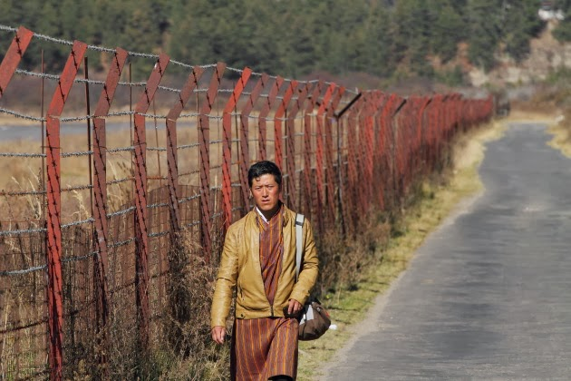 Local man walking past the tiny Bumthang airport of Bhutan