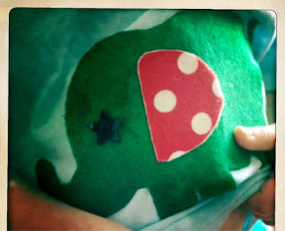 close up on the star eye, spotty ear and finish to the green felt elephant
