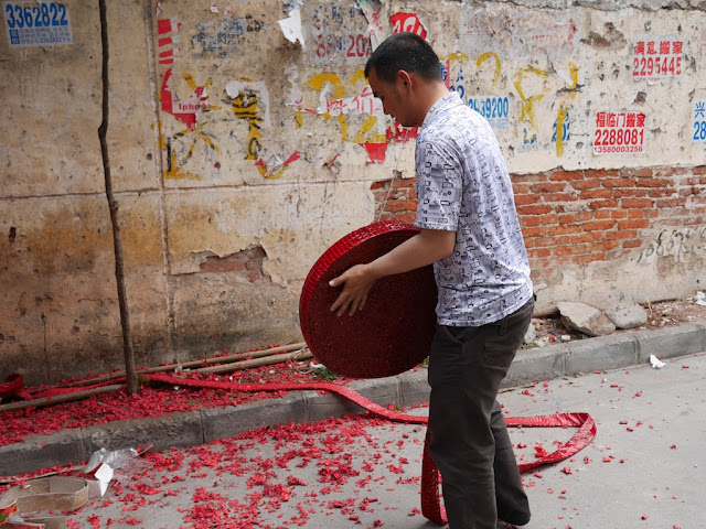 man with large roll of red firecrackers