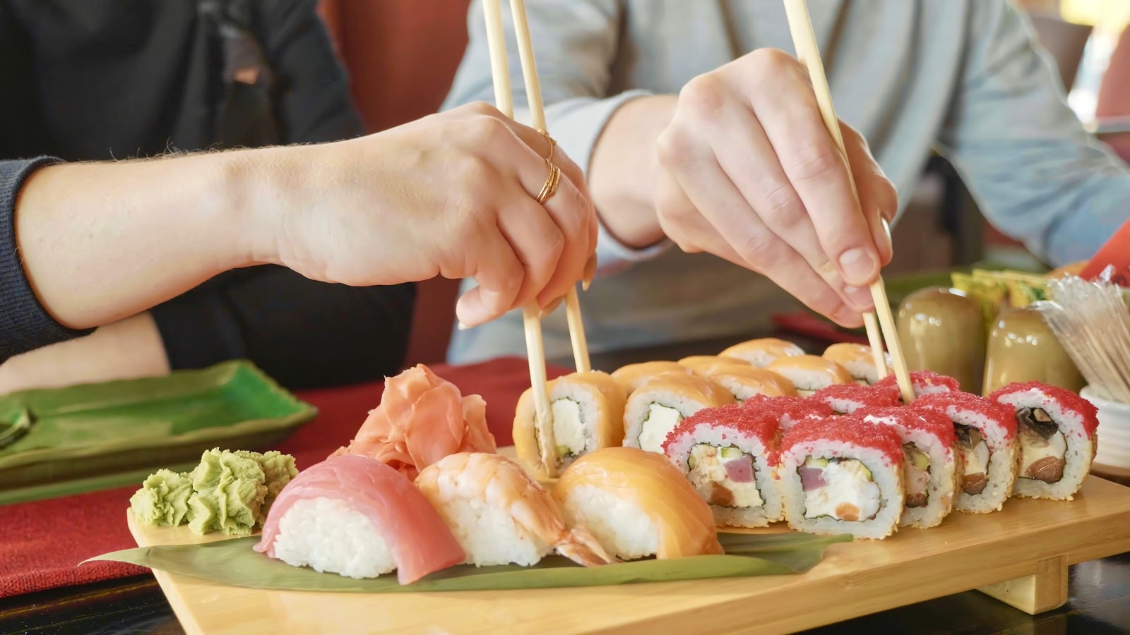 Japanese people eating sushi in the restaurant by using chopsticks.
