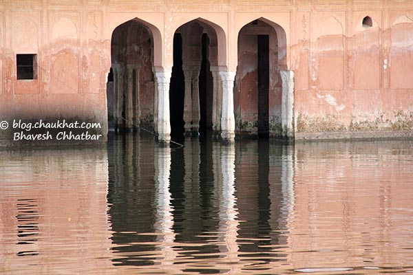 Reflection of a water-bordered pink monument near Jal Mahal of Jaipur