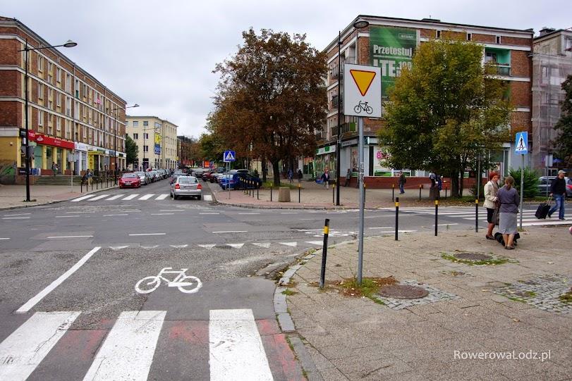 Śluza rowerowa i znak mówiący że trzeba ustąpić pierwszeństwa.
