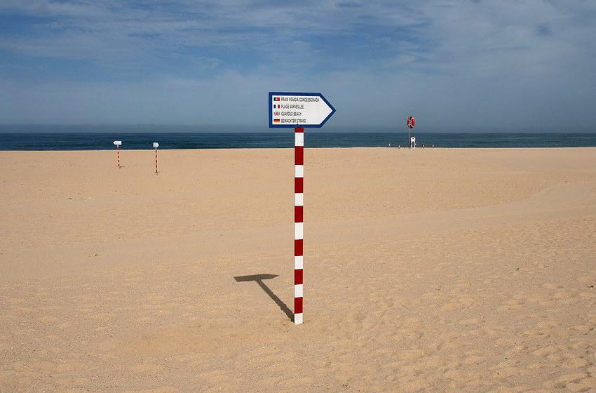 Praia deserta com uma placa ao centro apontando para a direita. Ao fundo à esquerda mais duas placas e à direita o posto de socorro. Por fim, o mar calmo e céu azul