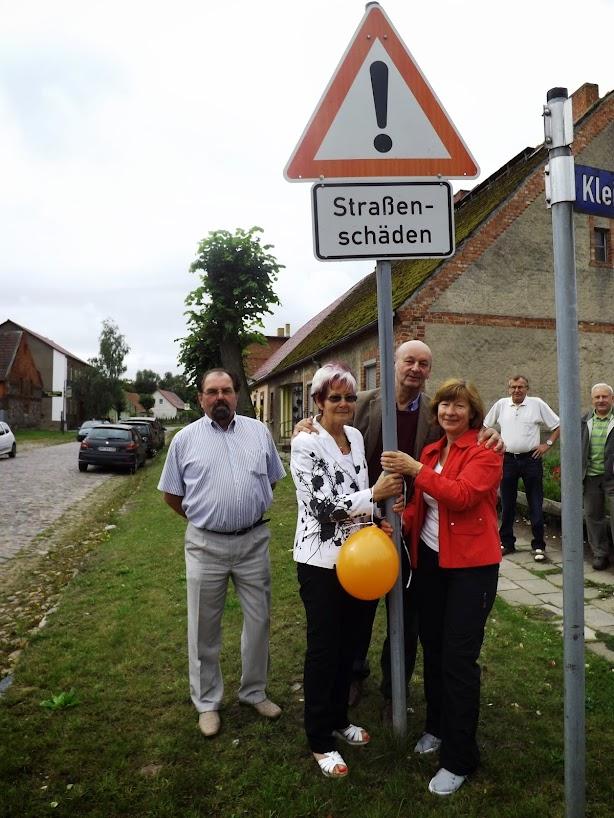 Casekower Bürgermeisterin und Gemeindevertreter aus Wartin rütteln gemeinsam am verhaßten Schild (Bild: A.M.)
