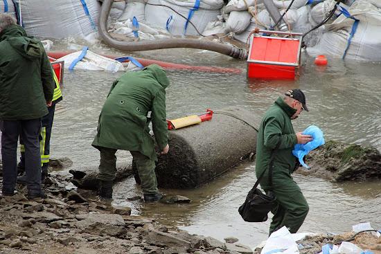 Drei Männer im flachen Wasser an einer badewannengroßen Luftmine.