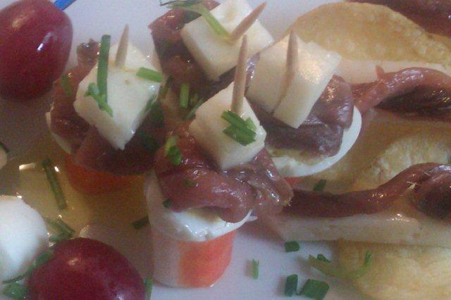 Aperitivos variados de anchoas y huevos de codorniz con queso de cabra