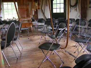 De touwen van het luiwerk hangen tussen de stoelen.