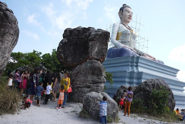 tourists near some rocks and a statue