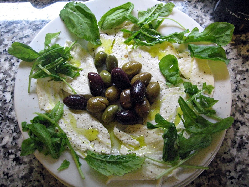 Fresh, whole, cow's, milk Mozzarella with olives and arugula - dressed with extra virgin olive oil, sea salt, and freshly cracked black pepper (the pepper is optional)