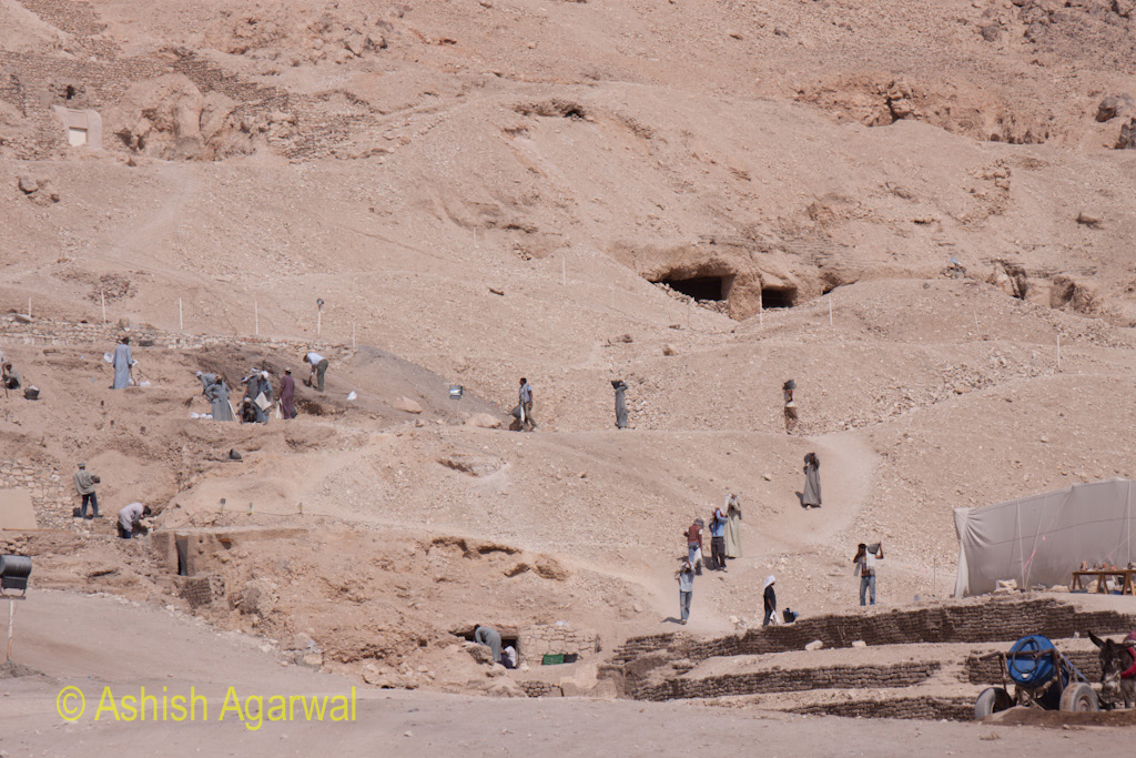 Workers on the excavation and restoration team, working on the limestone cliffs outside Luxor