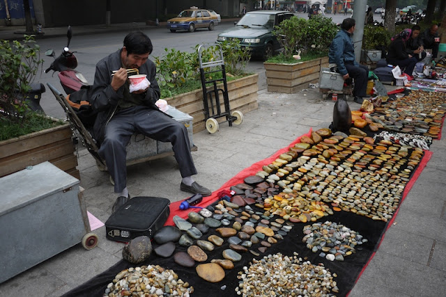 man eating lunch while selling small stones outside Tianxinge Antique City in Changsha, China