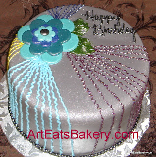 Purple fondant birthday cake with blue and teal flower and royal icing squiggles