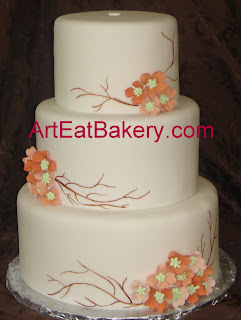 Three tier round fondant wedding cake with custom peach and salmon dogwood flower design and hand painted twigs