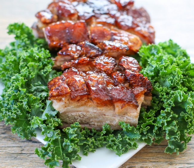 slices of crispy pork belly with sriracha glaze on a bed of fresh greens
