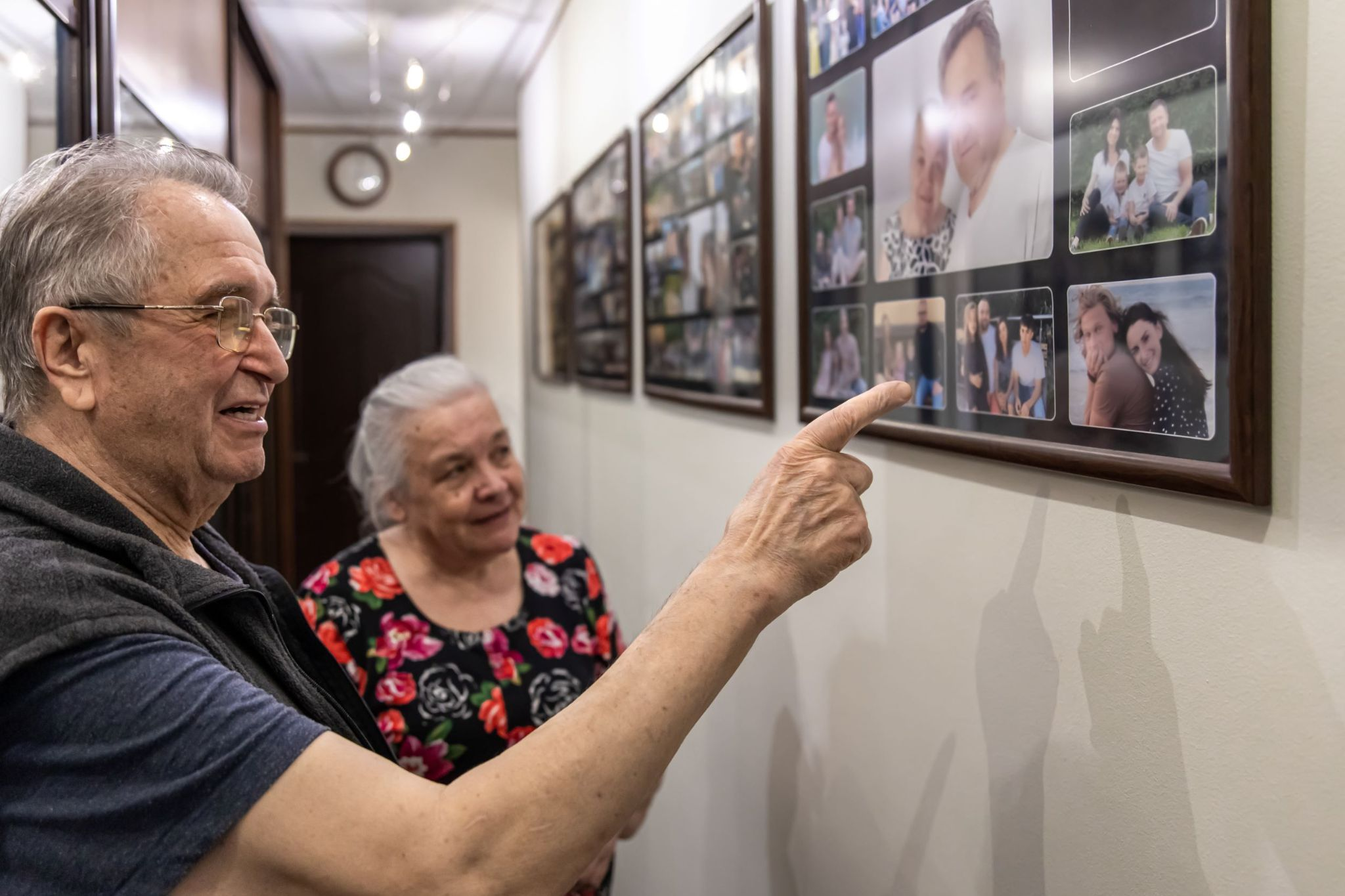 older-couple-looking-at-family-photos-on-wall