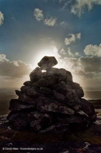 Pile of rocks haloed with sunlight against a cloudy blue sky