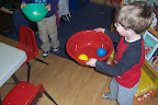 Child twirls light plastic balls in bowls to see and feel the motion.