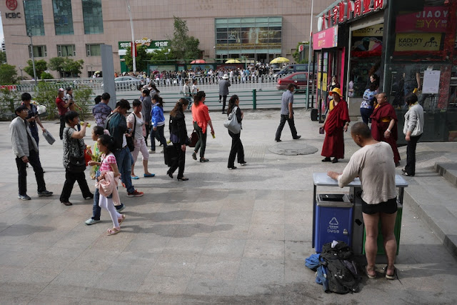 people walking on sidewalk and man standing in his underwear in Xining, Qinghai, China