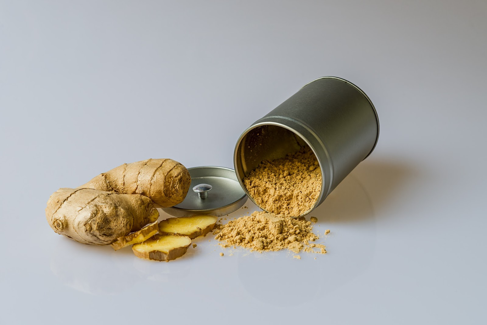 Fresh ginger beside a tin of ground ginger, ready to add to a healthy meal.