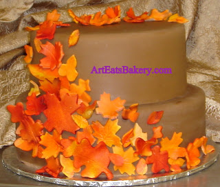 Brown fondant round two tier wedding cake with handmade orange, red and yellow suger fall leaves design