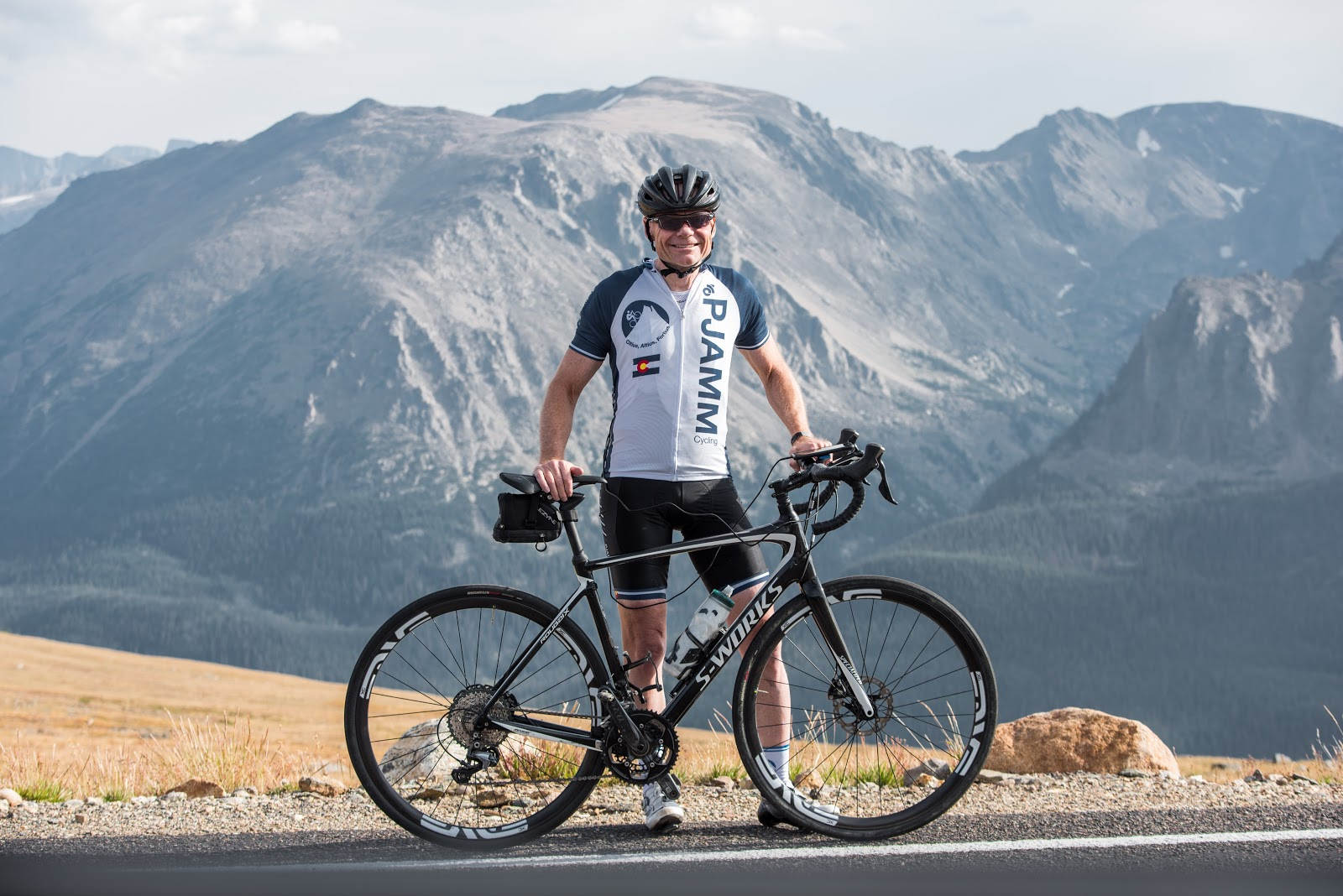 John Johnson PJAMM Cycling with bike at high point of Trail Ridge bike climb