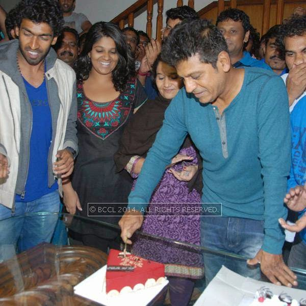 Shivarajkumar cuts a birthday cake as Dhruva Sarja, Vinay Raghavendra and Geetha Shivarajkumar look on during his birthday celebrations in Bangalore.