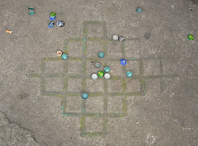 board game on the sidewalk using bottle caps