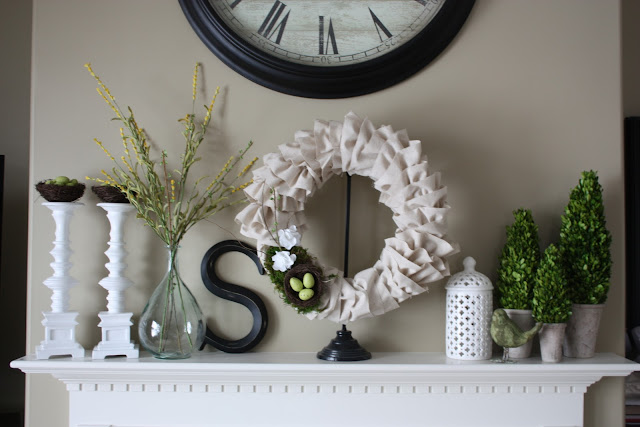 A white fireplace mantel with the white wreath on it, a vase with flowers, topiaries and a clock on the wall above it.
