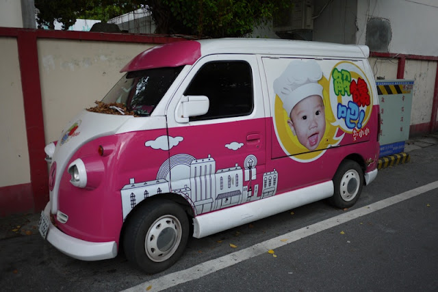 van with large face of a happy baby with a chefs hat