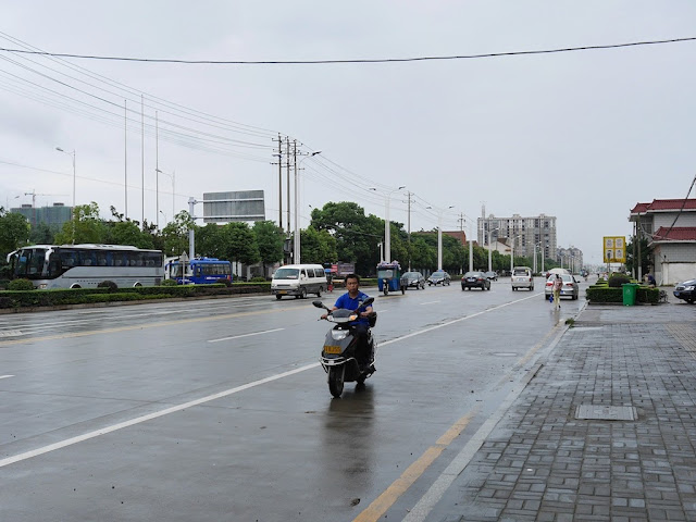 man riding a motorbike on a wide street