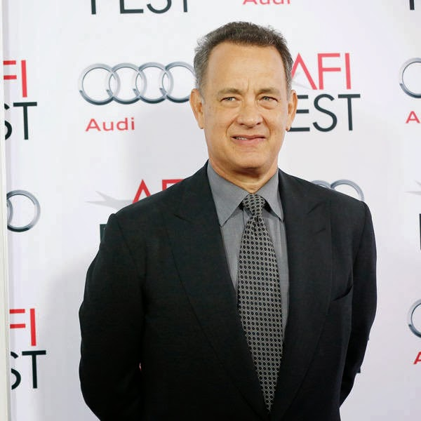 Tom Hanks poses at the premiere of Saving Mr. Banks during the opening