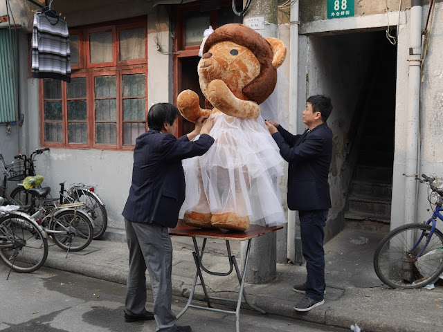 two men altering a wedding dress for a large stuffed bear