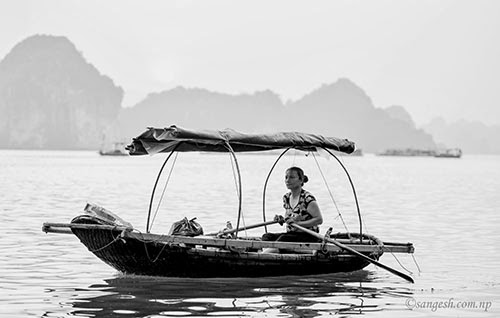 A lady rowing a Boat in Ha Long Bay