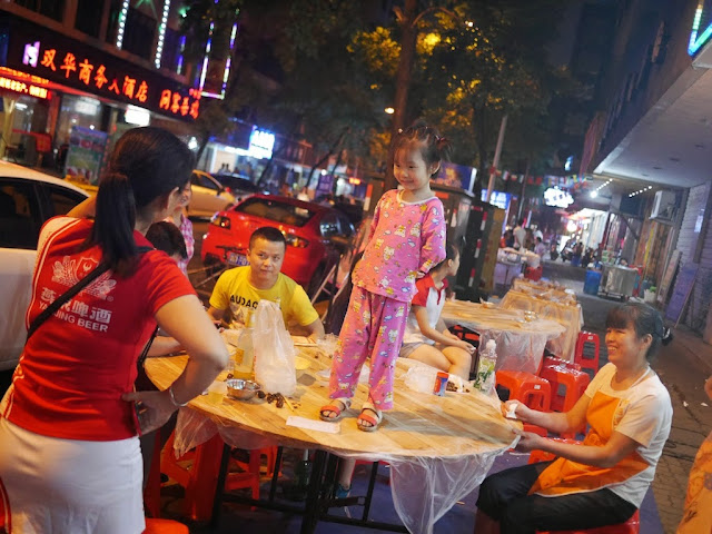 little girl standing on an outdoor restaurant table in Hengyang