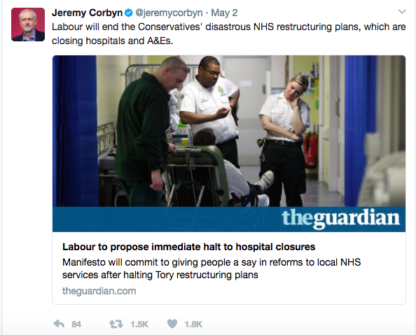 "Screenshot of Jeremy Corbyn UK Labour Party Leader Tweet ""Labour will end the Cpnservatives' disastrous NHS restructuring plans, which are closing hospitals and A&E's"" Picture of man in wheelchair being looked at by Ambulance staff in a reception area of a hospital - Story is from the Guardian newspaper"