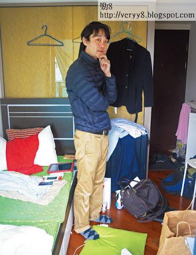以月租九千元租住禦悅最小單位的日本人松田憲明,聽見記者想了解貴價劏房情況,即展示其淩亂不堪的私竇,基本上這間屋的「客飯睡」房面積,在這張相中已一眼睇曬。(黃叔榮攝)